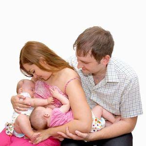 双子に授乳するお母さん