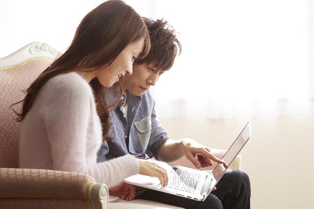 パソコンを見る夫婦