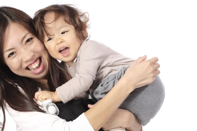2歳児を抱っこするお母さん