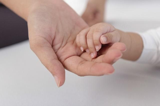 赤ちゃんの手を握るお母さん