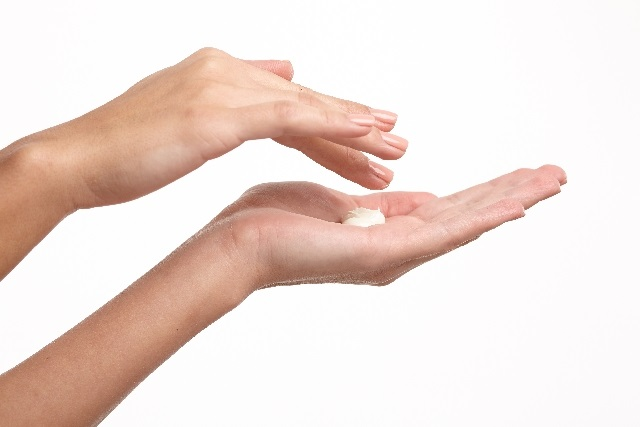 手のクリームをとる女性