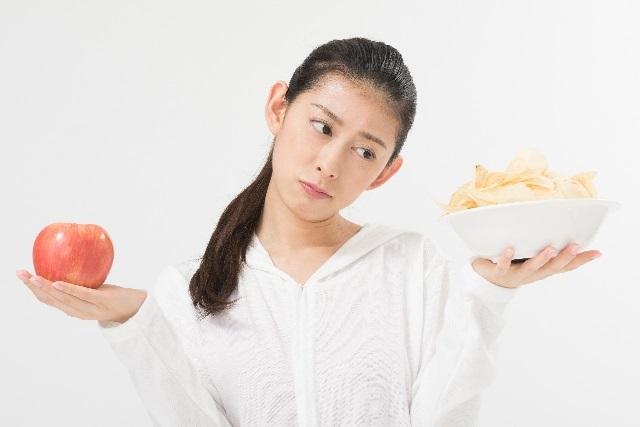 ポテトチップを我慢する女性