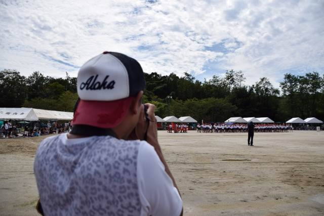 運動会で撮影しているお父さん
