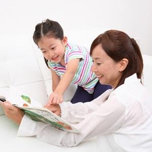 絵本を読む3歳児とお母さん